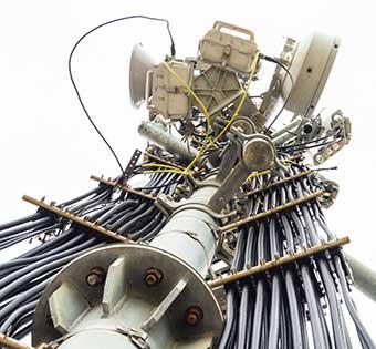 Blick von unten nach oben zu Richtfunkantennen und Versorgungskabeln