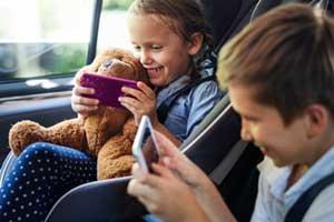 Kinder spielen am Smartphone im PKW