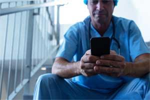 Krankenhausarzt in einer Pause am Smartphone