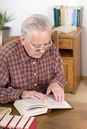 Mann liest Buch in Bibliothek